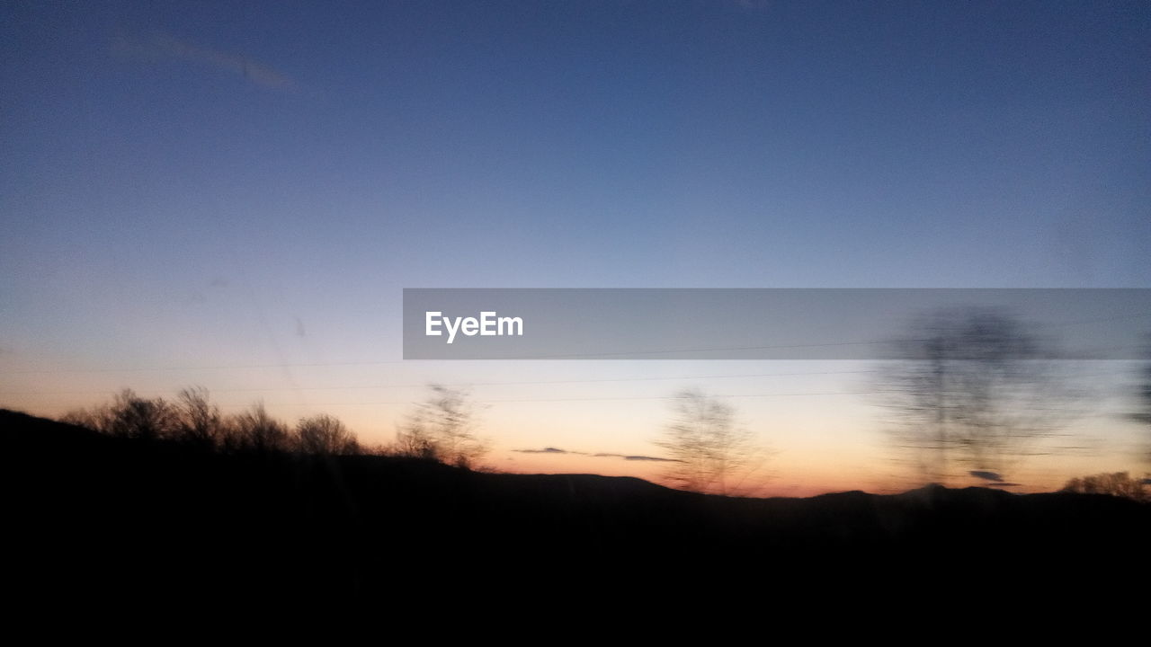 sky, silhouette, tranquility, copy space, beauty in nature, tranquil scene, scenics - nature, sunset, no people, nature, tree, landscape, non-urban scene, environment, plant, outdoors, clear sky, idyllic, dark