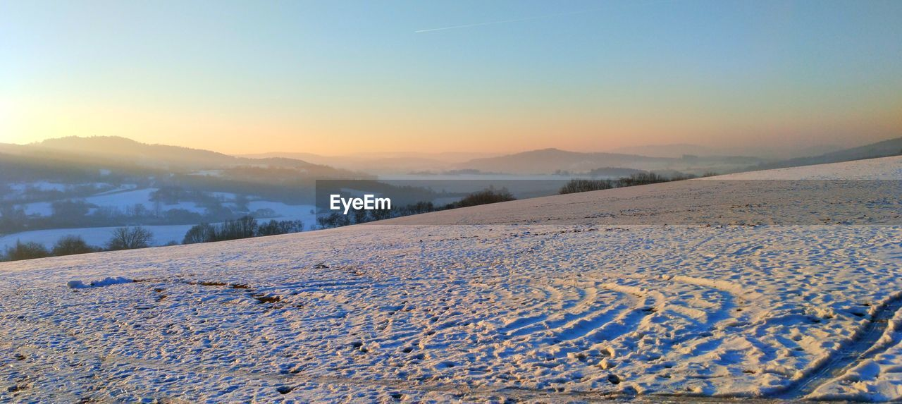 snow, winter, cold temperature, tranquil scene, nature, tranquility, scenics, beauty in nature, landscape, weather, no people, sky, field, outdoors, clear sky, day, sunset, mountain