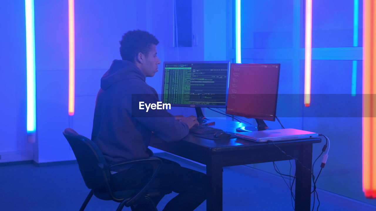 Young man in hood hacking by using computer while sitting at illuminated office