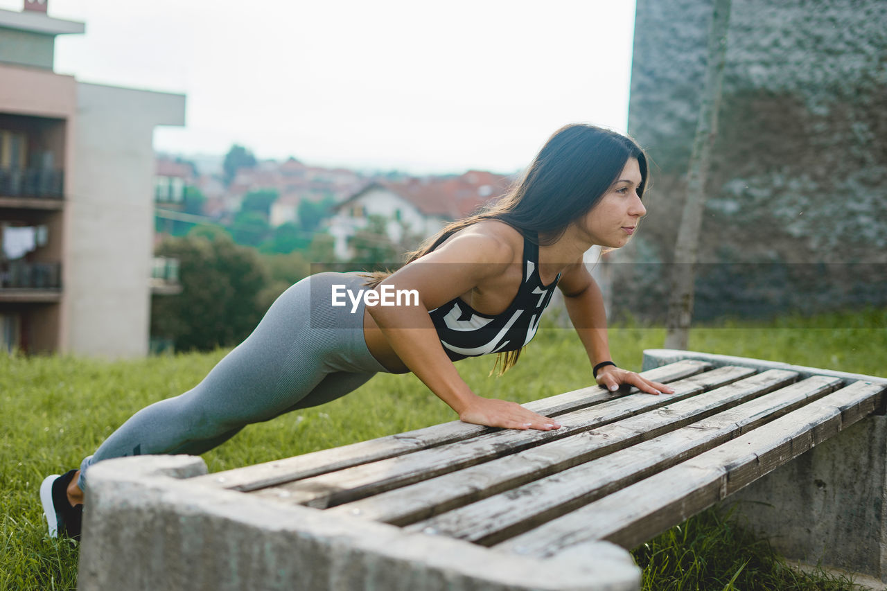 Woman exercising by bench on field