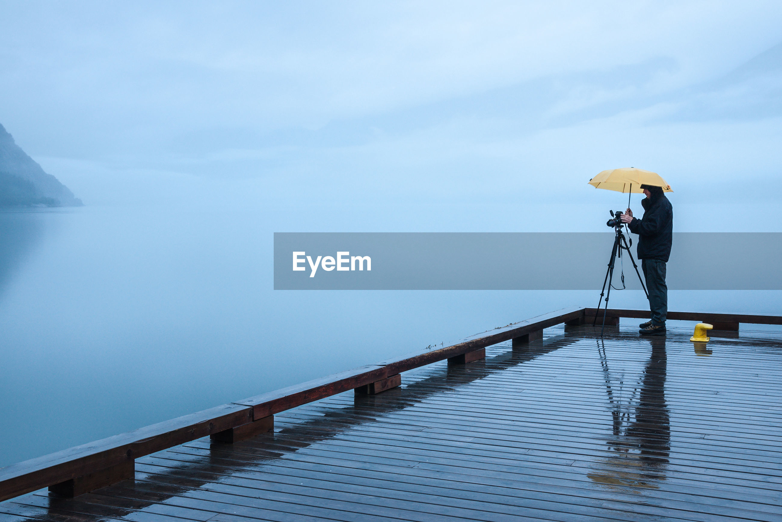 Full length of man standing on pier with tripod and umbrella during monsoon
