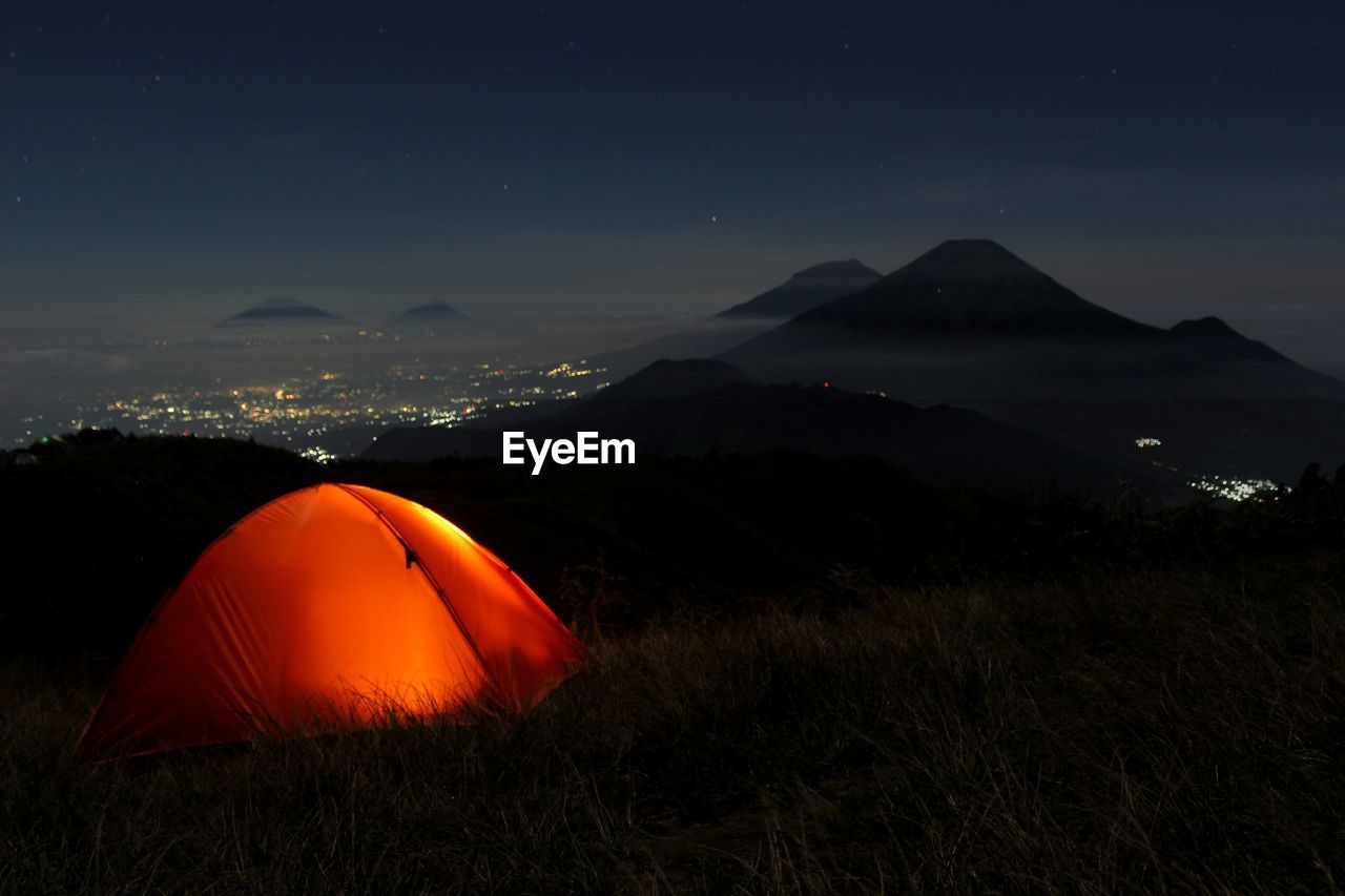 Illuminated tent on field against sky at night