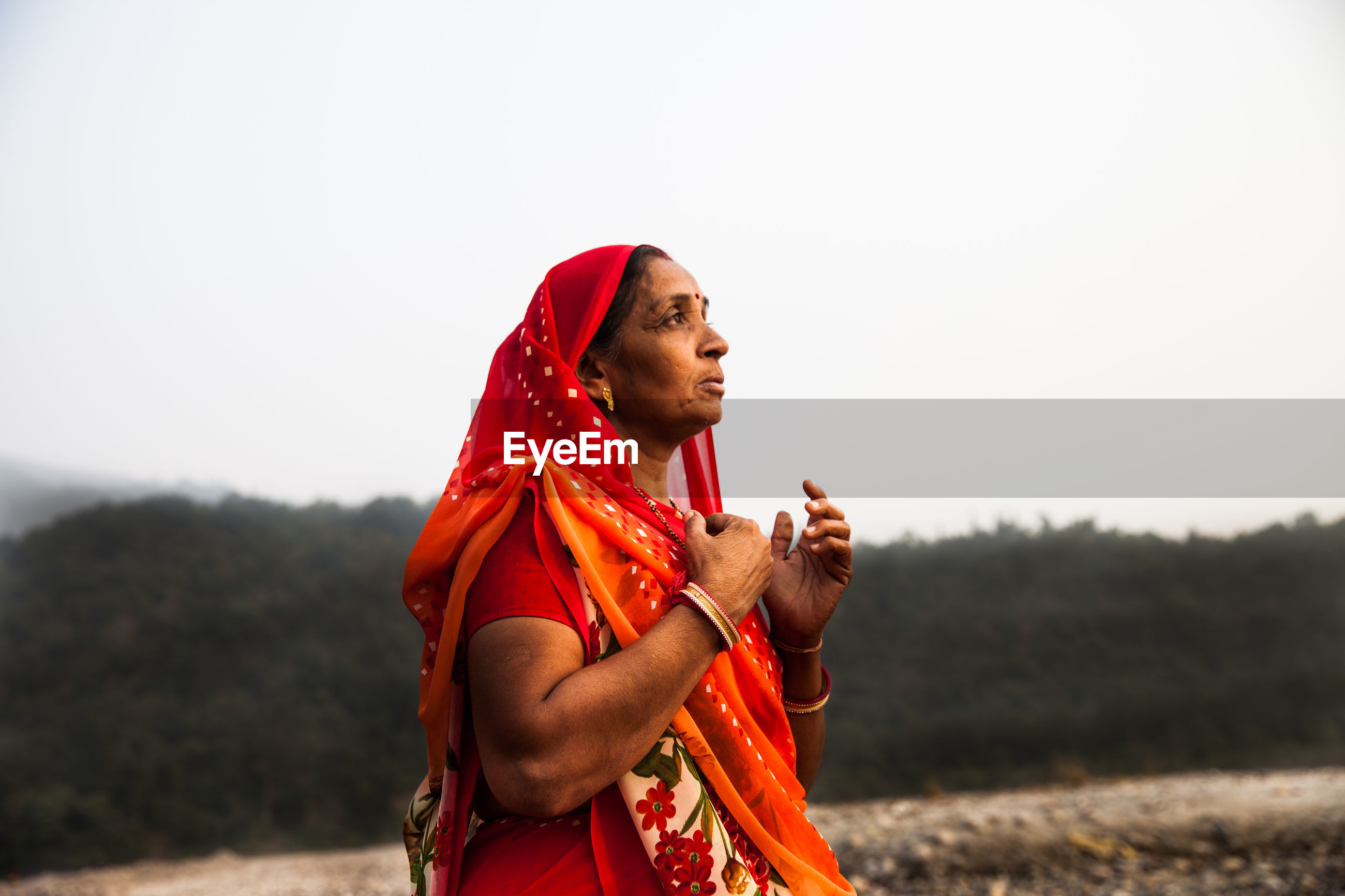 YOUNG WOMAN LOOKING AWAY ON FIELD AGAINST SKY