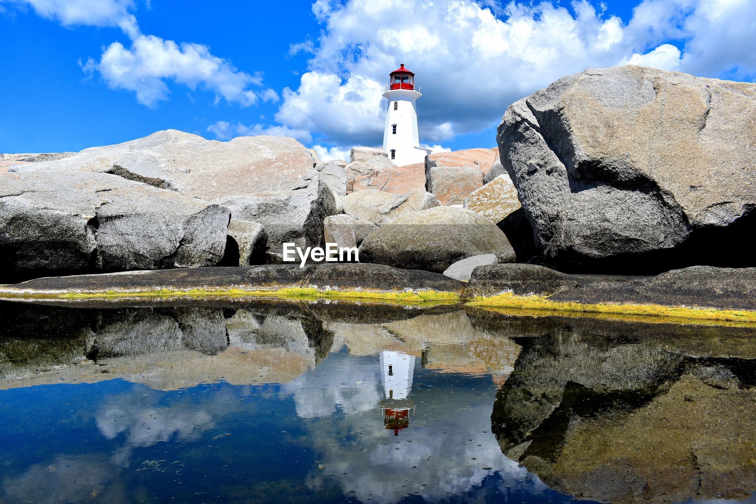 Reflection of lighthouse on sea against blue sky