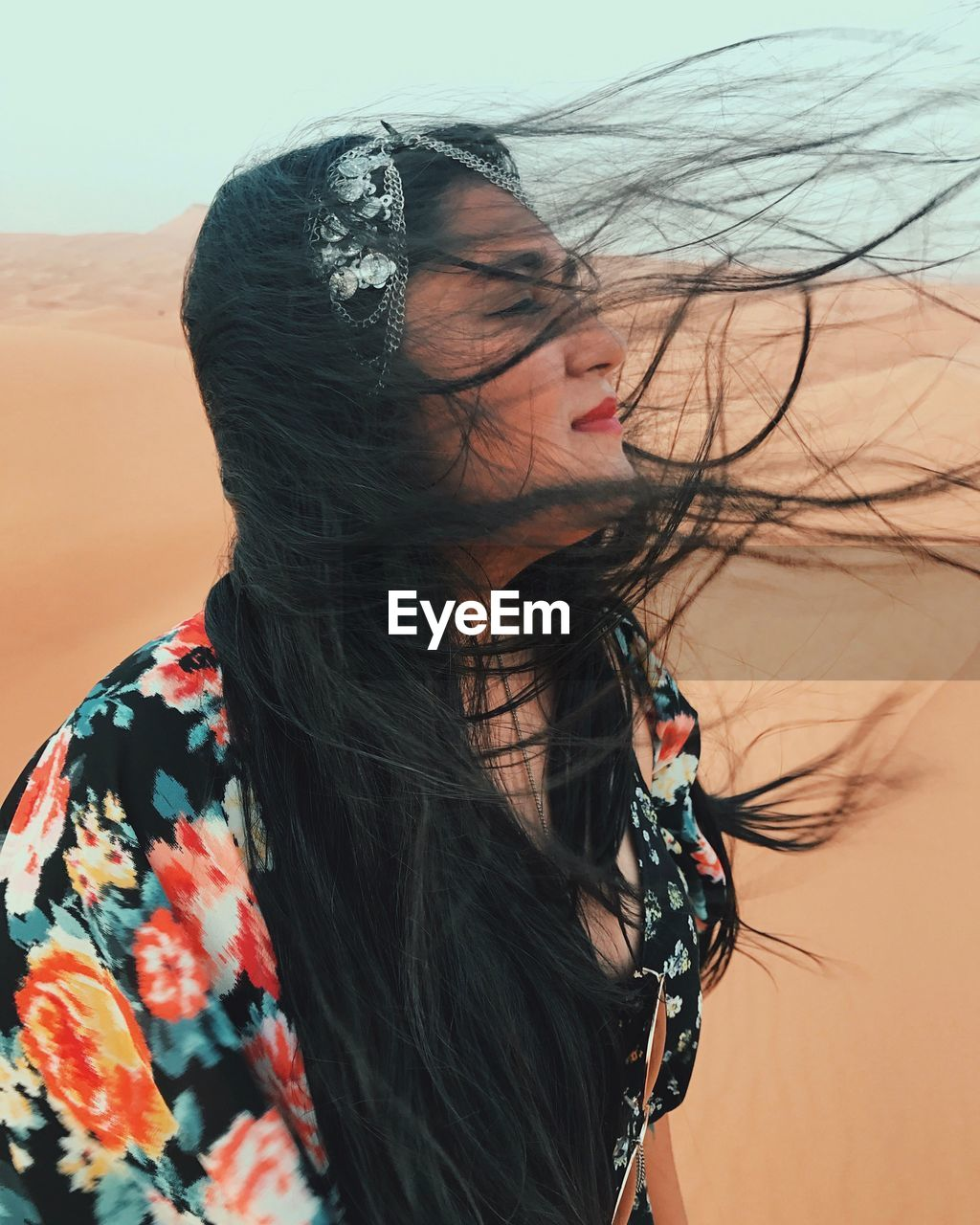 Young woman on sand in desert against sky
