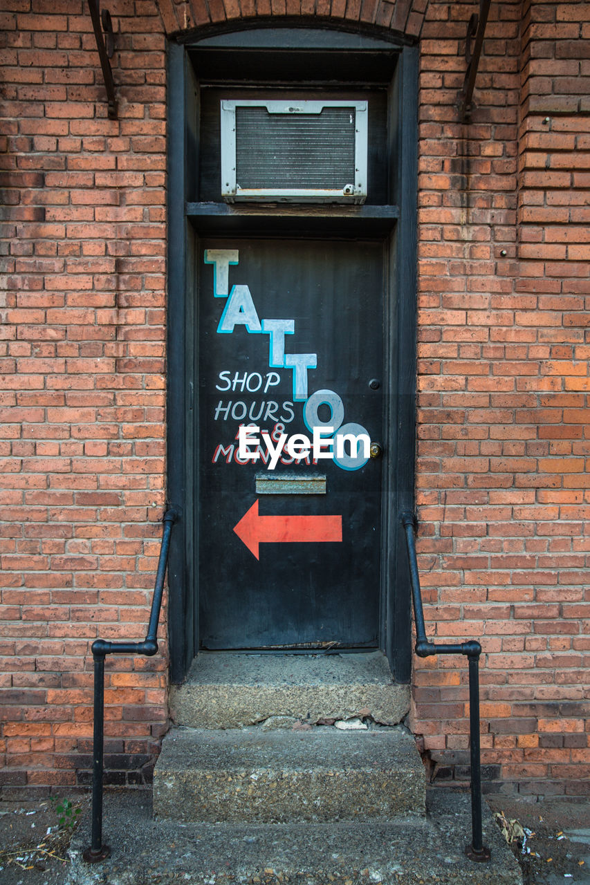 architecture, communication, wall, brick, sign, brick wall, building exterior, built structure, text, western script, no people, wall - building feature, day, entrance, door, information, arrow symbol, direction, building, closed, outdoors