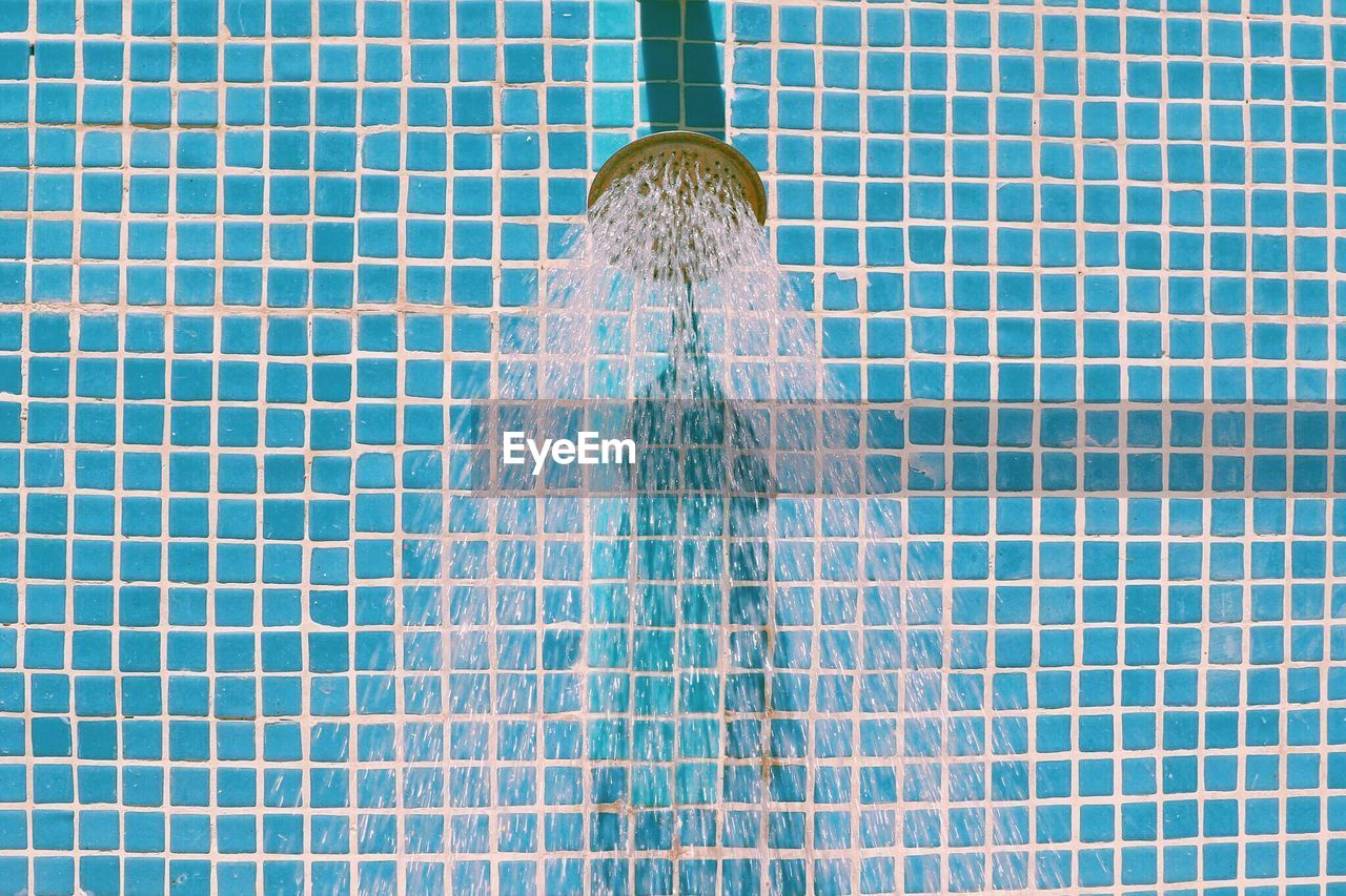 Close-up of water running from shower head in bathroom