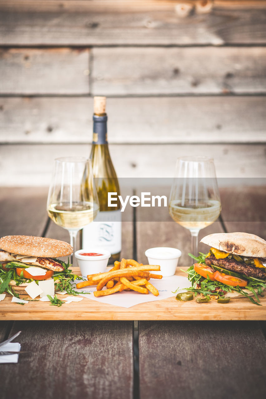 food and drink, refreshment, table, wine, drink, alcohol, food, bottle, freshness, indoors, glass, wineglass, wood - material, still life, ready-to-eat, container, glass - material, plate, fast food, serving size, no people, table knife, red wine