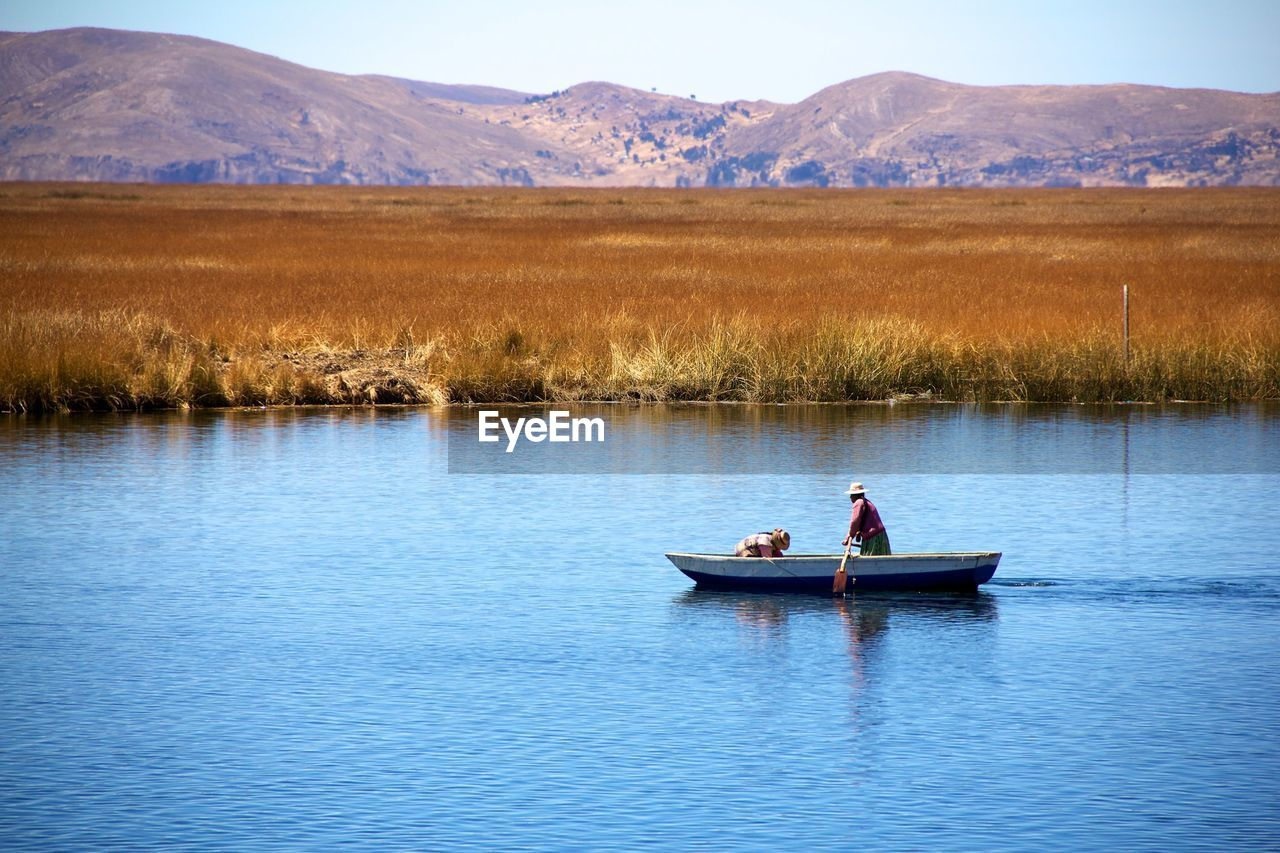 People rowing boat in river against mountains