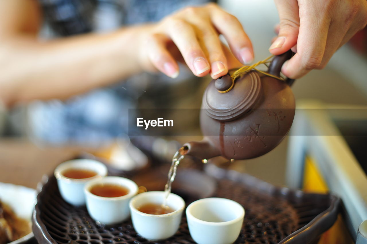 Midsection Of Man Pouring Chinese Tea From Teapot In Cup At Home