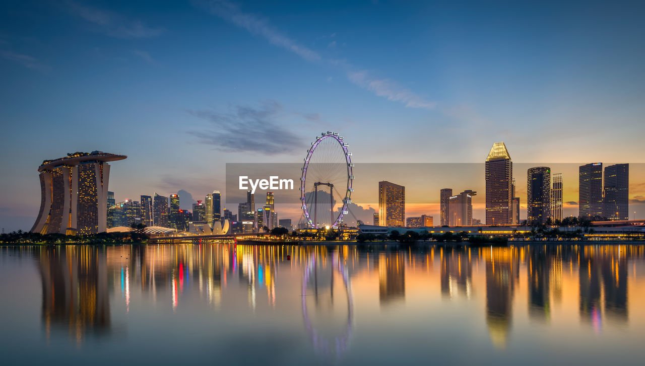 sky, built structure, architecture, building exterior, city, water, reflection, waterfront, amusement park, building, ferris wheel, office building exterior, amusement park ride, urban skyline, nature, cityscape, skyscraper, landscape, travel destinations, no people, tall - high, modern, outdoors, financial district