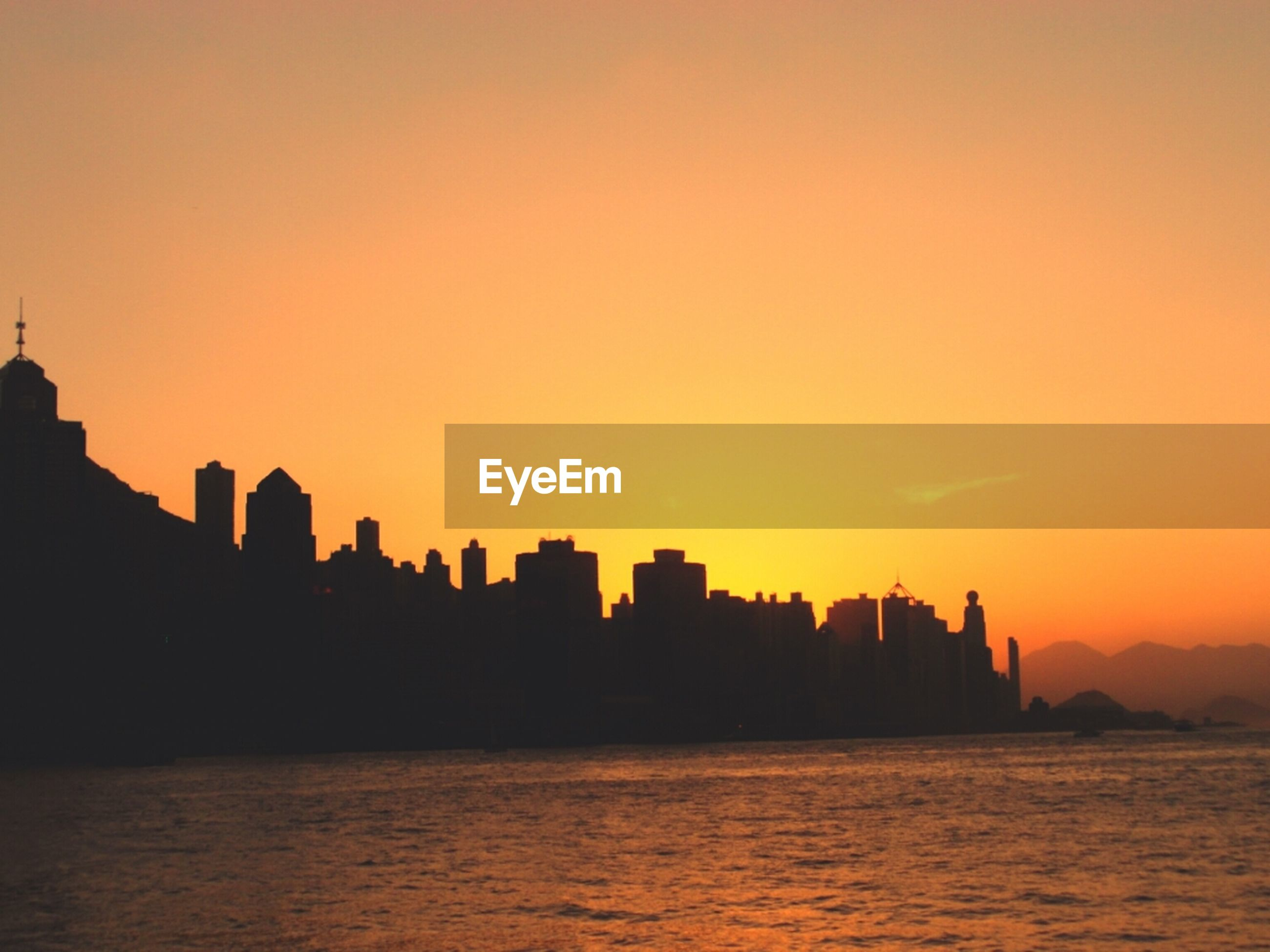 sunset, silhouette, waterfront, building exterior, architecture, water, orange color, built structure, copy space, sea, city, clear sky, scenics, cityscape, beauty in nature, tranquility, sky, nature, tranquil scene, outdoors