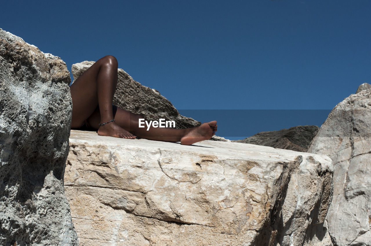 Low Section Of Woman Lying On Rock Against Clear Blue Sky