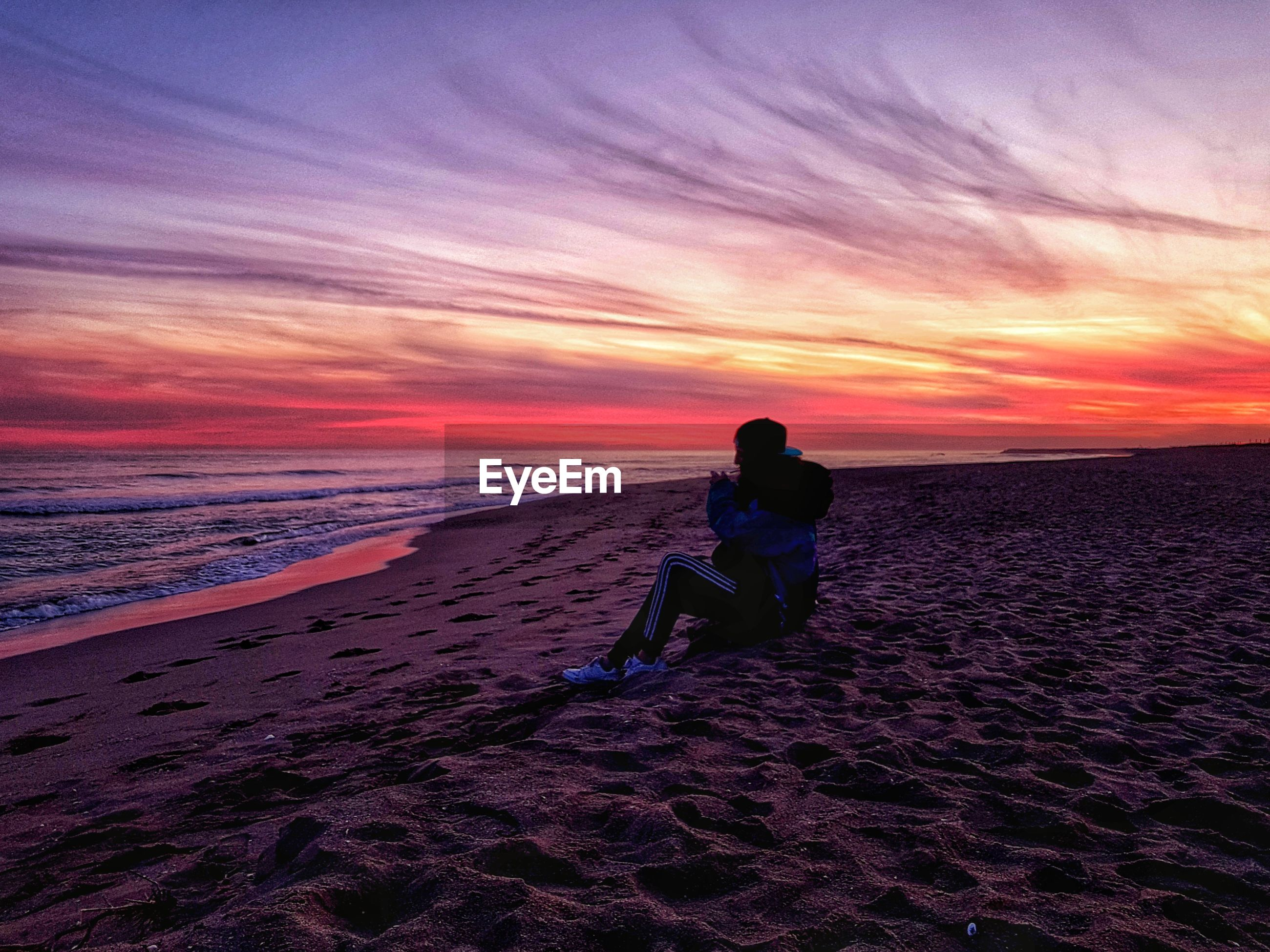Woman smoking on beach against sky during sunset