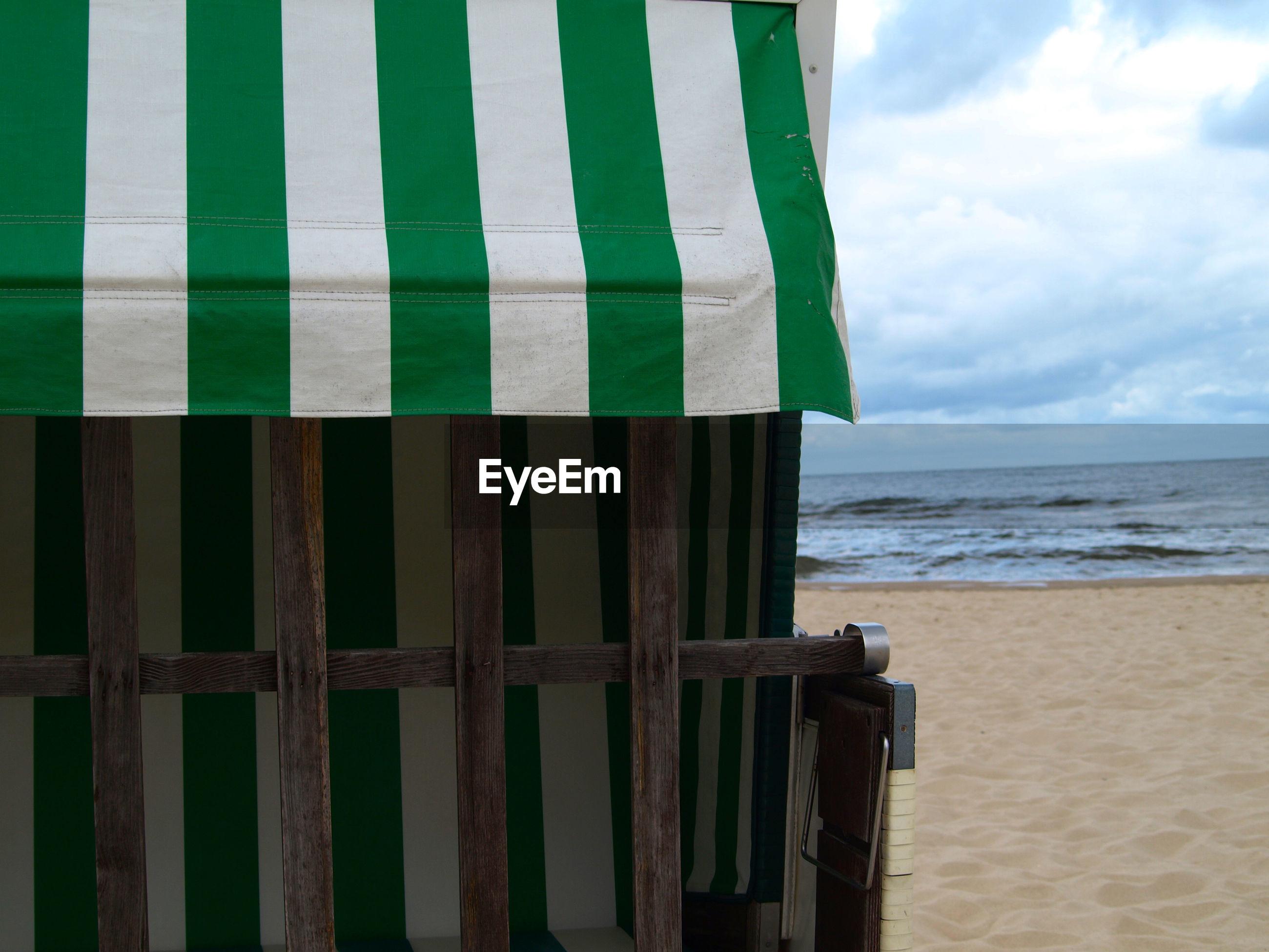 Close-up of hooded beach chair at beach