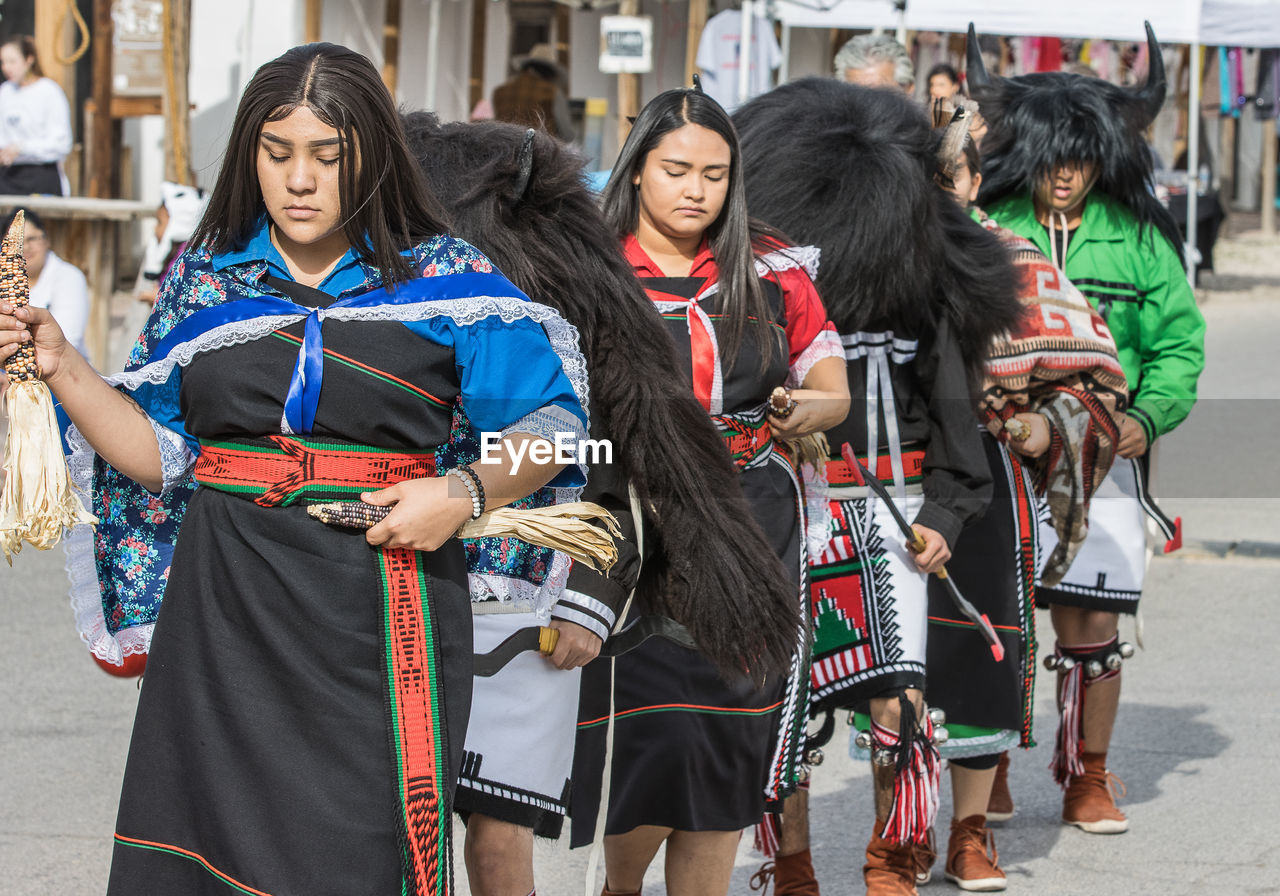 clothing, group of people, women, day, people, three quarter length, adult, real people, arts culture and entertainment, standing, traditional clothing, focus on foreground, costume, hair, city, front view, young women, young adult, long hair, hairstyle