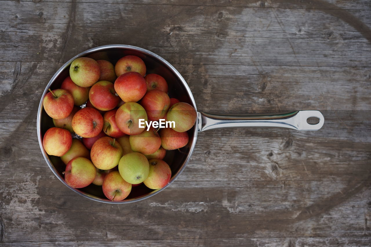High angle view of apples in pan on wooden table