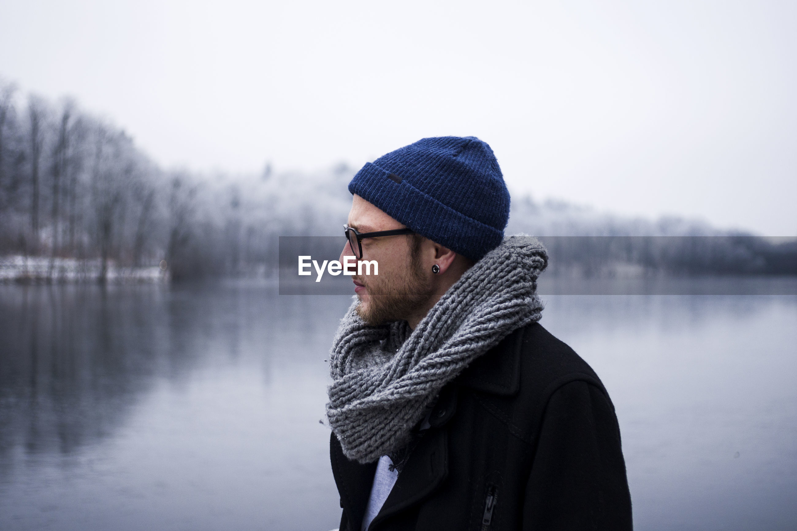 Young man looking away against lake and sky during winter