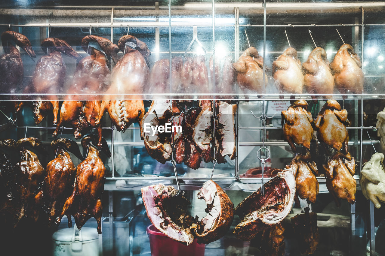 food and drink, meat, food, freshness, transparent, glass - material, retail, indoors, for sale, abundance, hanging, barbecue, grilled, choice, market, no people, shopping, retail display, reflection, roasted, sale, preparing food, display cabinet