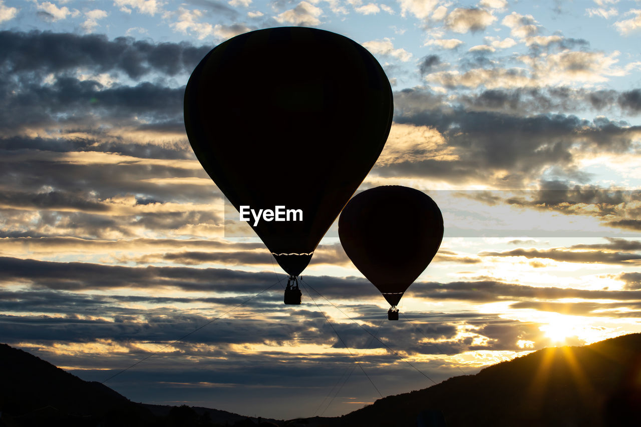 sky, balloon, cloud - sky, hot air balloon, sunset, air vehicle, scenics - nature, beauty in nature, nature, mountain, silhouette, orange color, transportation, flying, no people, mid-air, tranquility, environment, outdoors, tranquil scene, ballooning festival