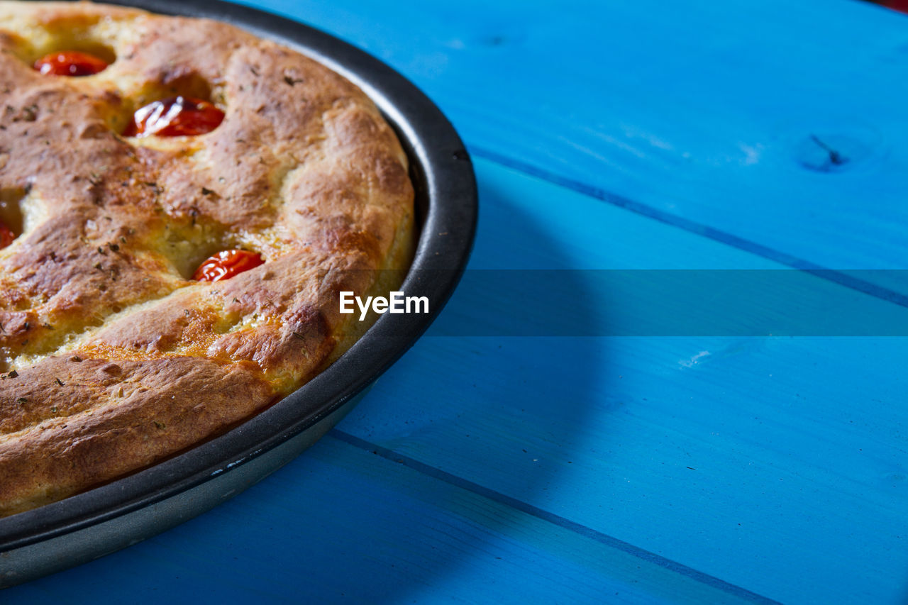 Cropped image of pizza made with tomatoes and oregano on blue table