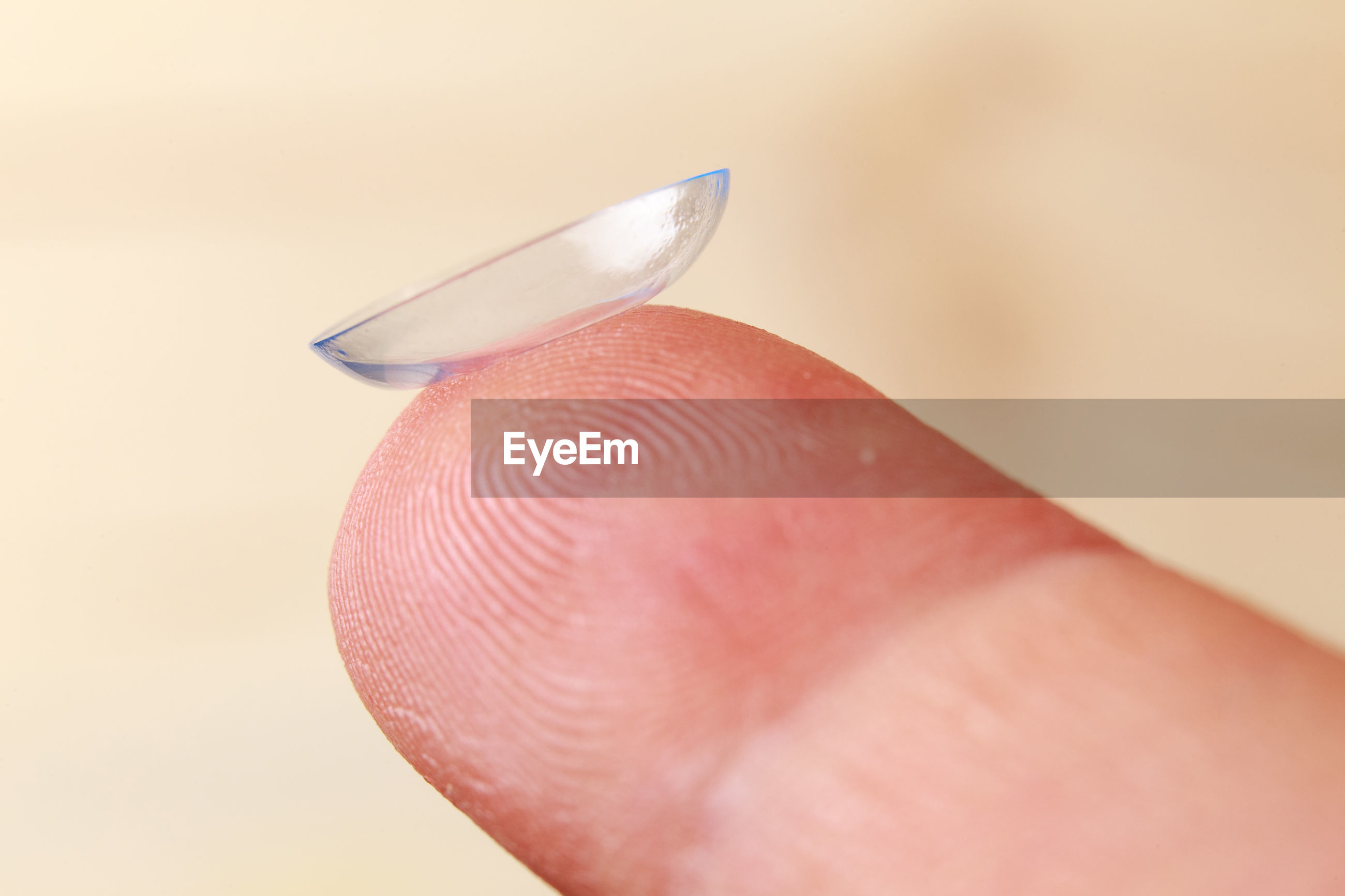 Close-up of hand holding contact lens over beige background