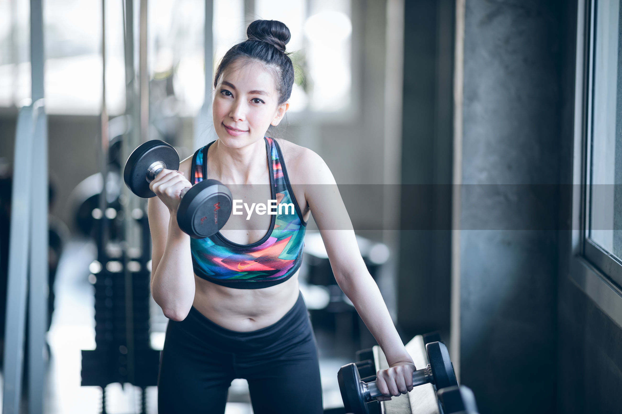 Portrait of woman exercising with dumbbells in gym