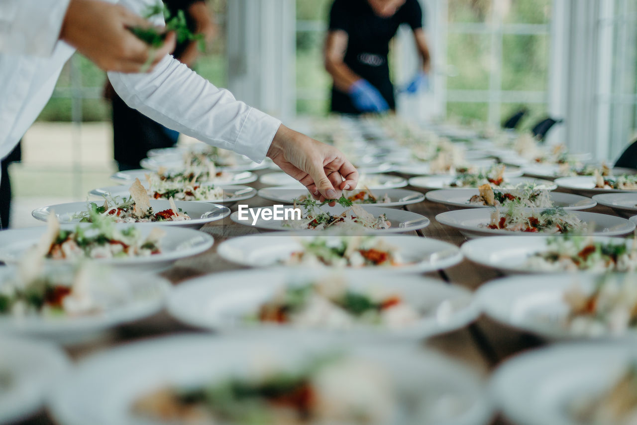 Midsection Of Man Serving Food In Plates On Table At Wedding Ceremony