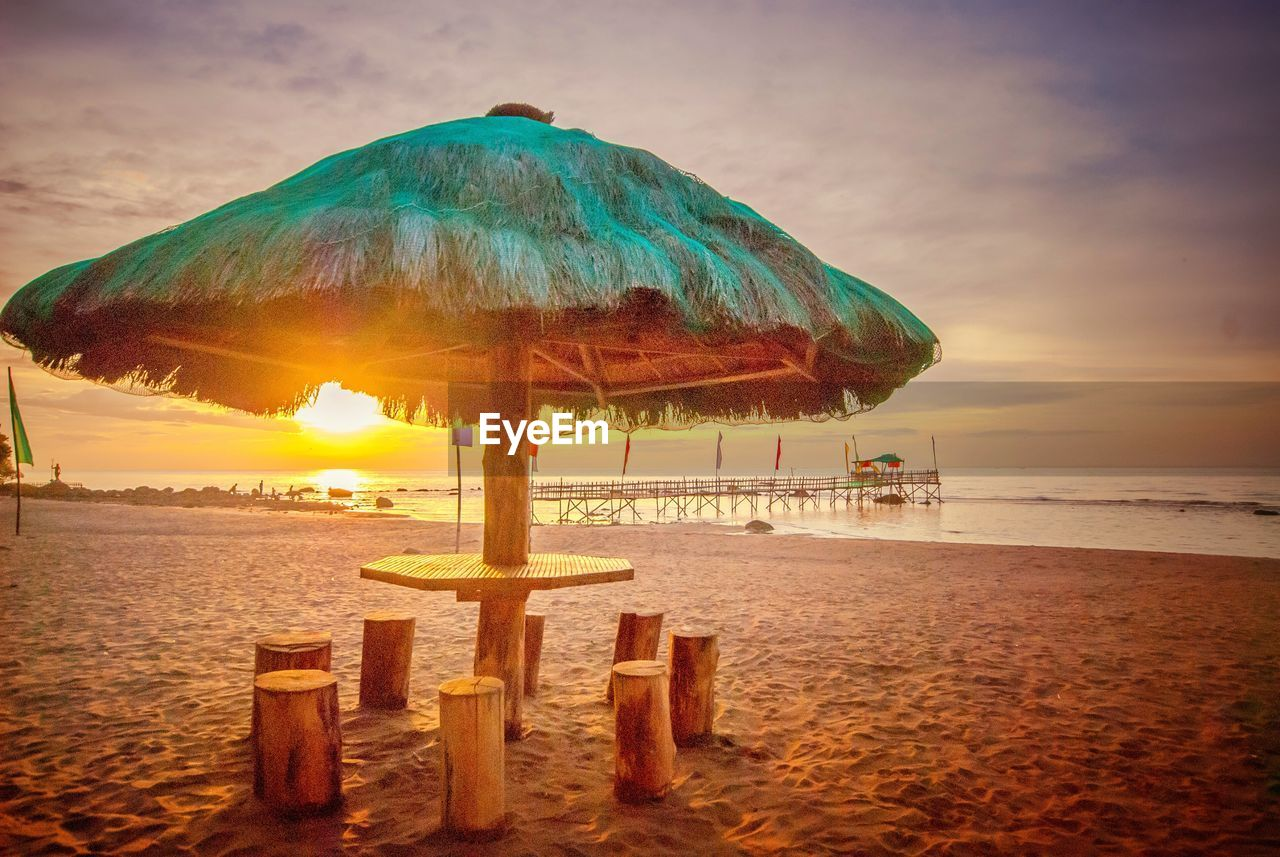 sea, beach, land, water, sky, horizon over water, sand, beauty in nature, horizon, scenics - nature, tranquil scene, thatched roof, sunset, chair, tranquility, nature, cloud - sky, roof, protection, no people, outdoors