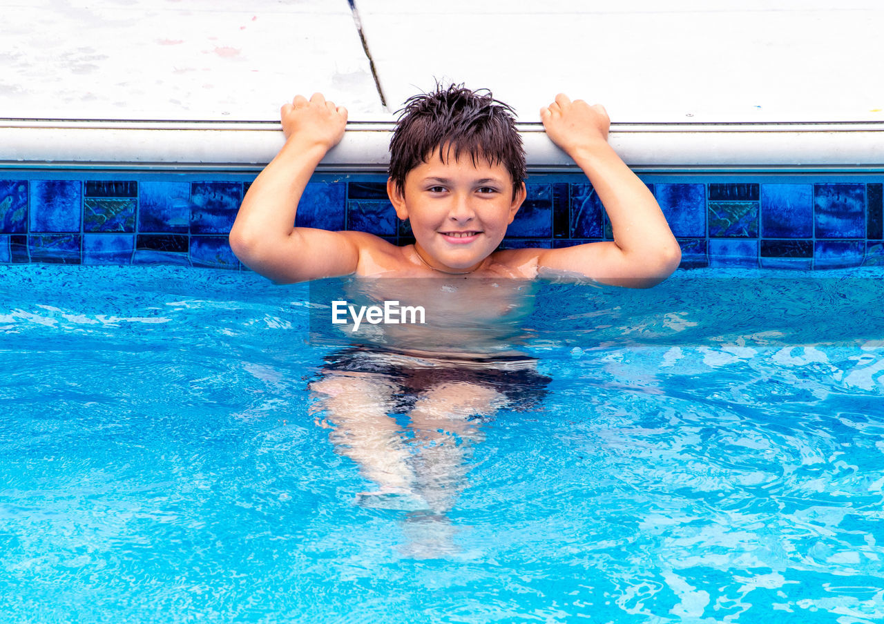 PORTRAIT OF HAPPY BOY IN SWIMMING POOL IN WATER