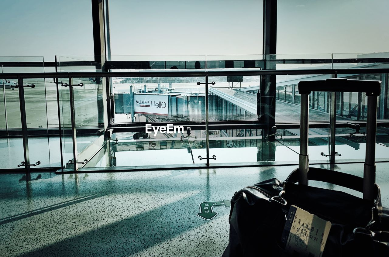 transportation, window, airport, glass - material, travel, transparent, mode of transportation, day, luggage, journey, outdoors, no people, architecture, railing, public transportation, nature, built structure, seat, airport departure area, waiting, airport terminal, station, leaving