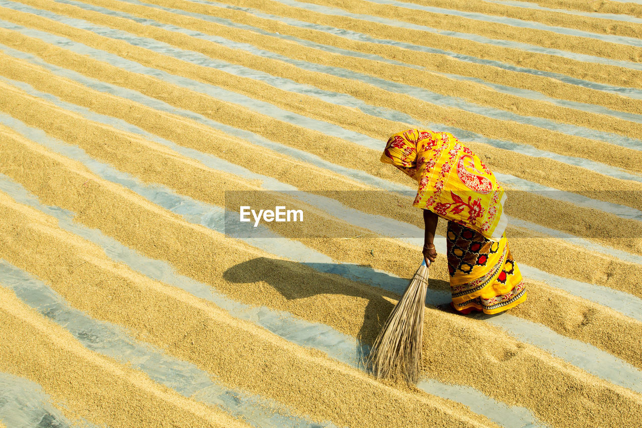 High Angle View Of Woman Sweeping Grains