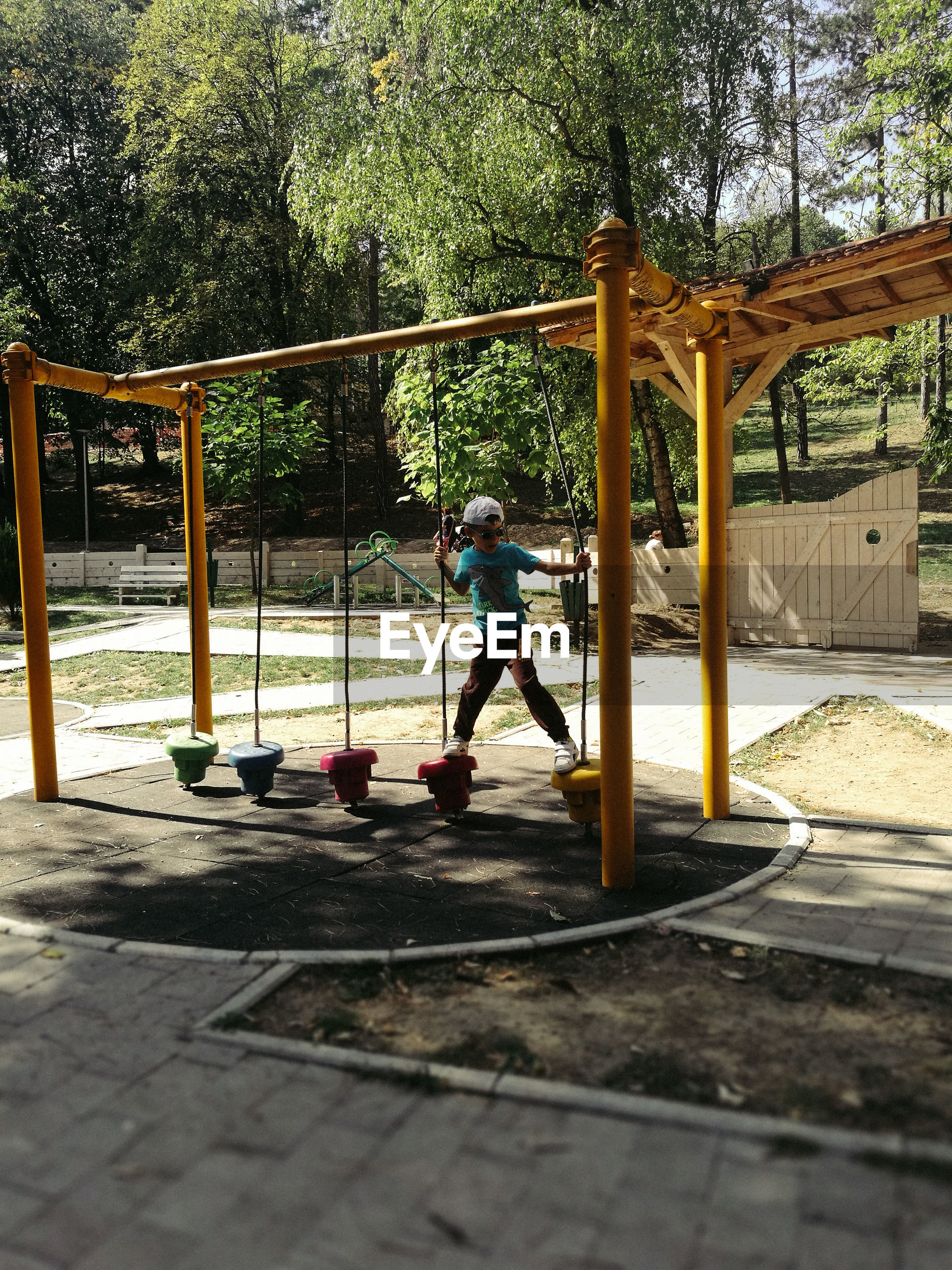 Boy playing with outdoor play equipment at playground