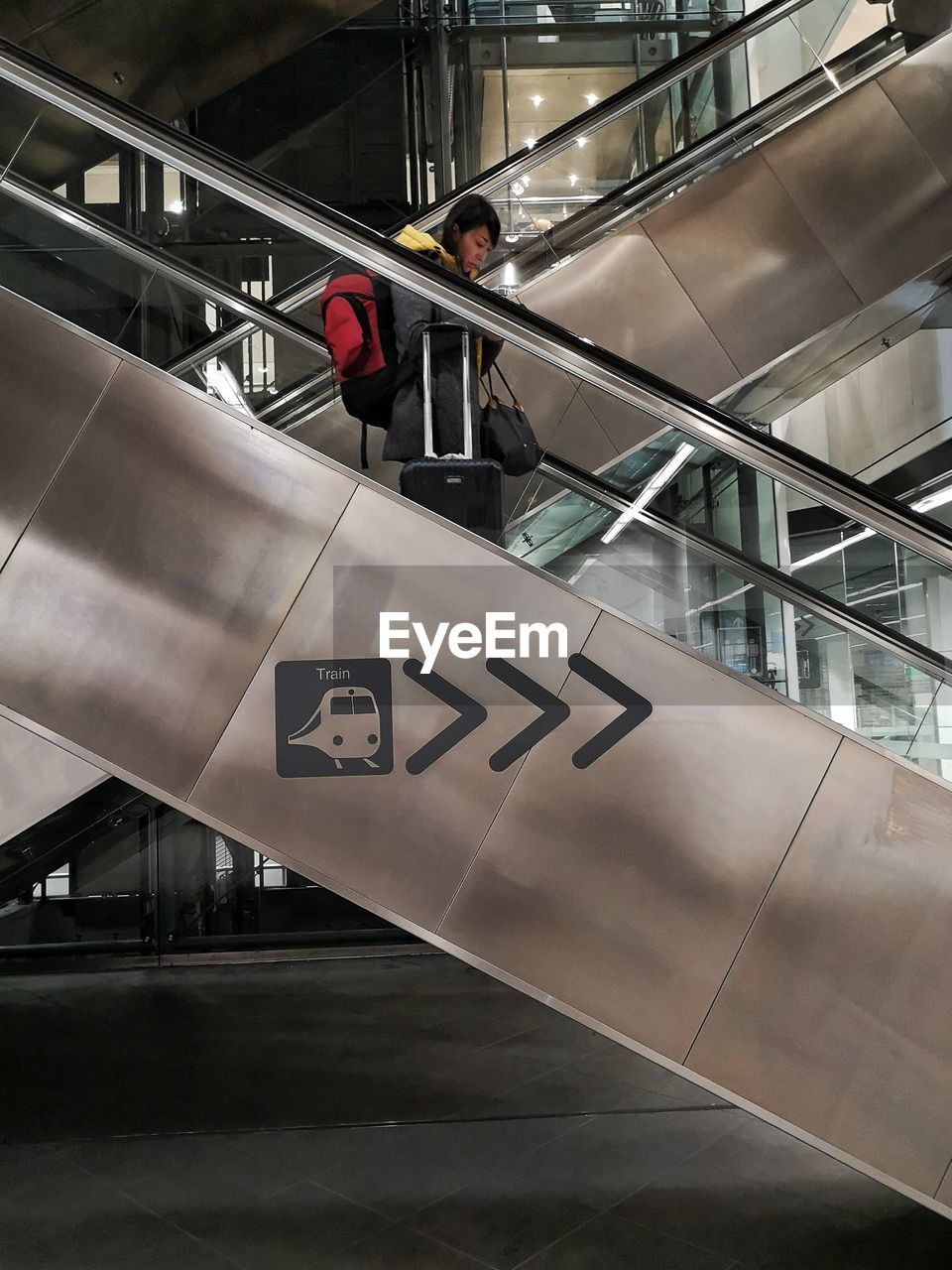 railing, architecture, real people, staircase, built structure, steps and staircases, indoors, one person, lifestyles, escalator, glass - material, men, full length, travel, transportation, moving up, communication, low angle view, sign, modern