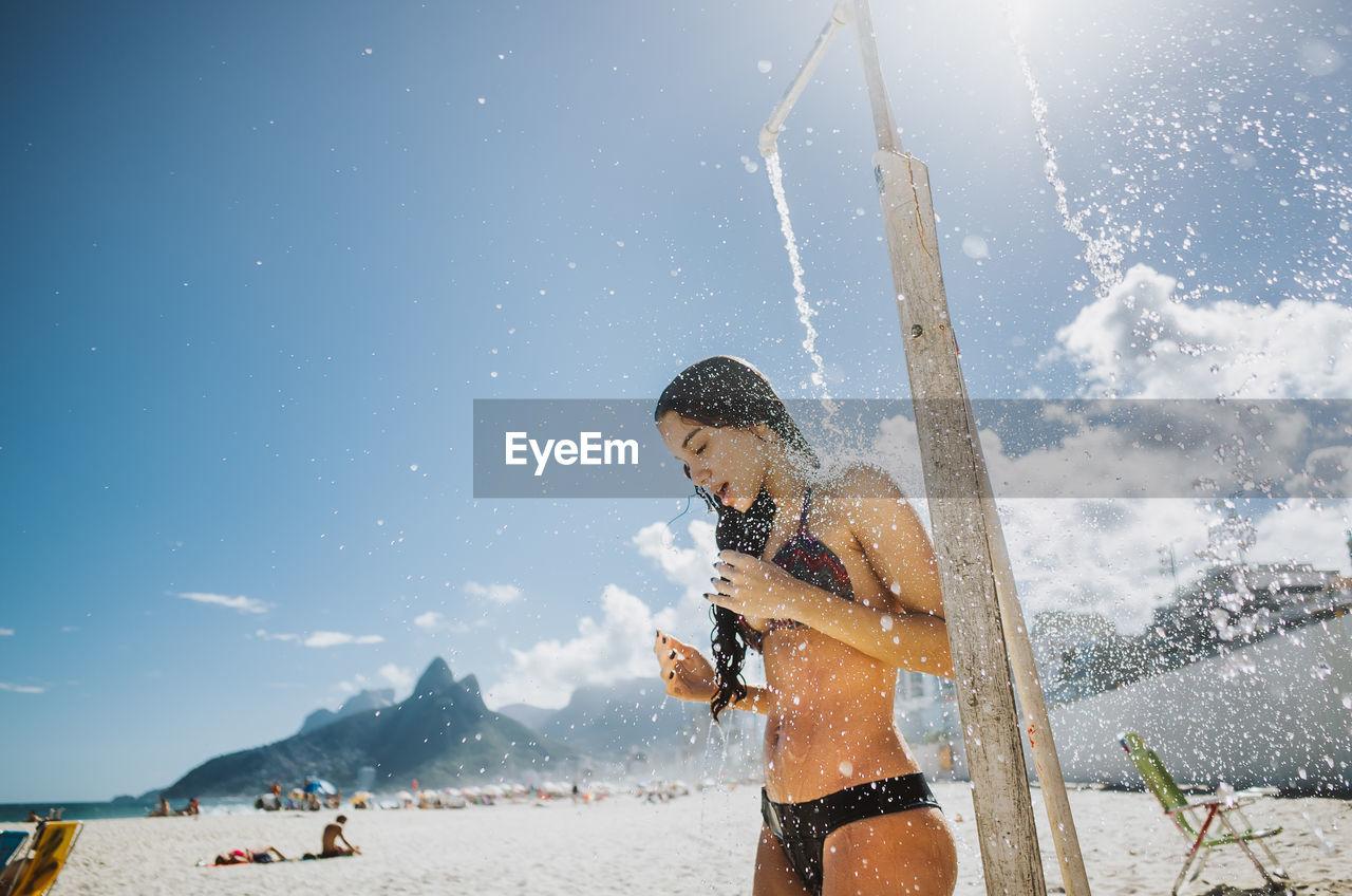Woman Bathing Below Shower At Beach Against Sky