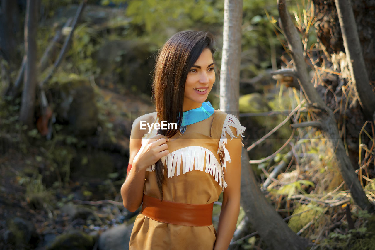 Smiling Young Woman In Traditional Clothing Standing Against Trees