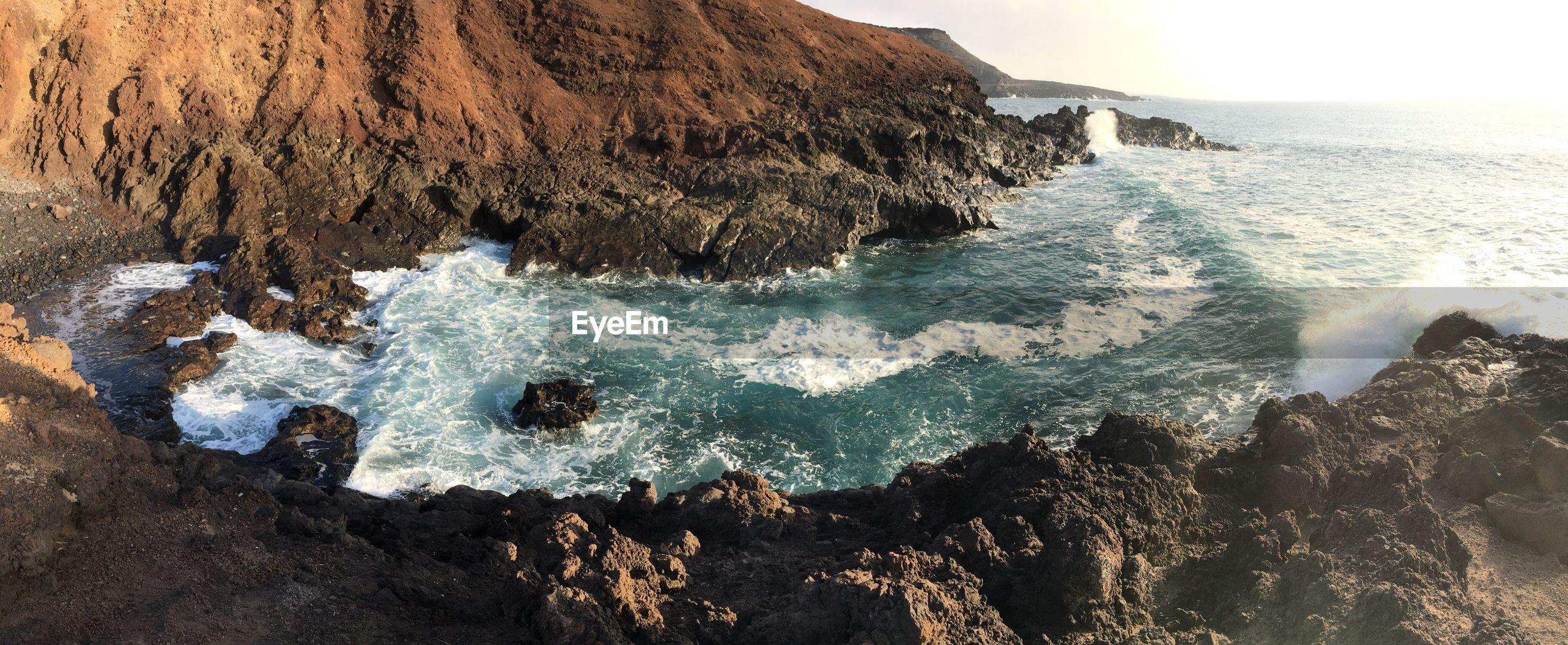 VIEW OF CALM BEACH AGAINST ROCKY COASTLINE