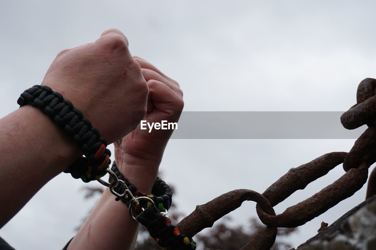 Cropped Hands Attached With Metallic Chain Against Sky