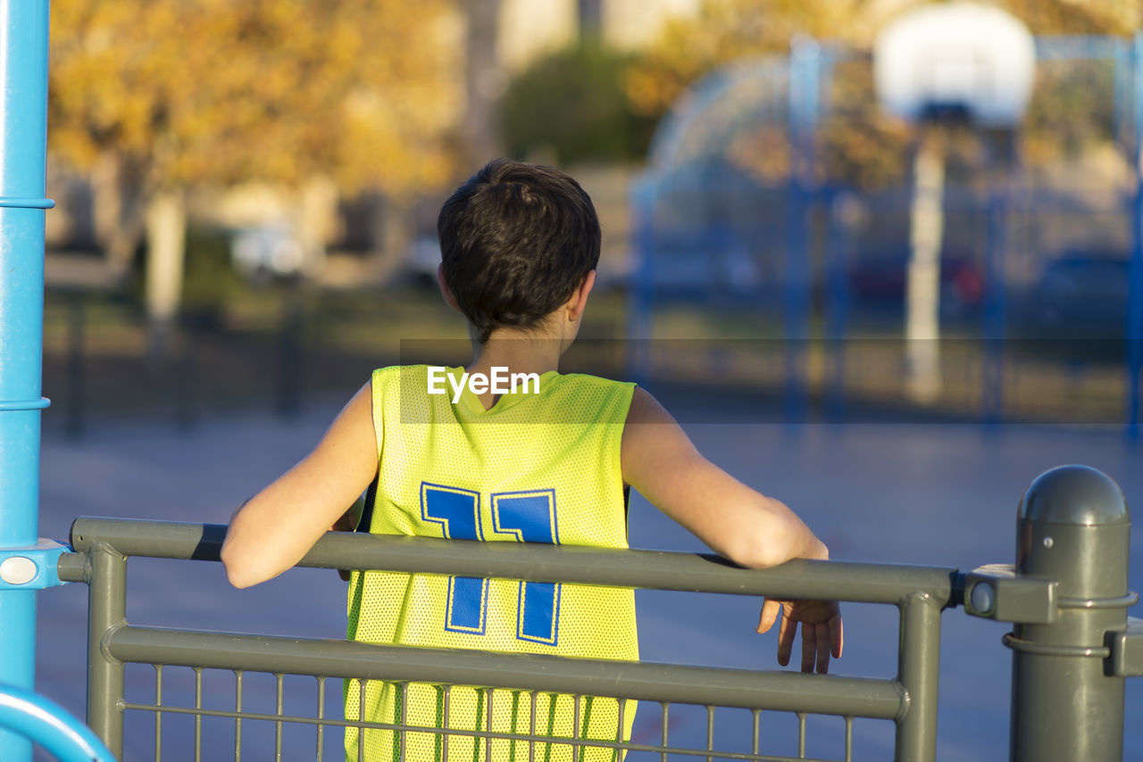 Rear View Of Boy Leaning On Railing