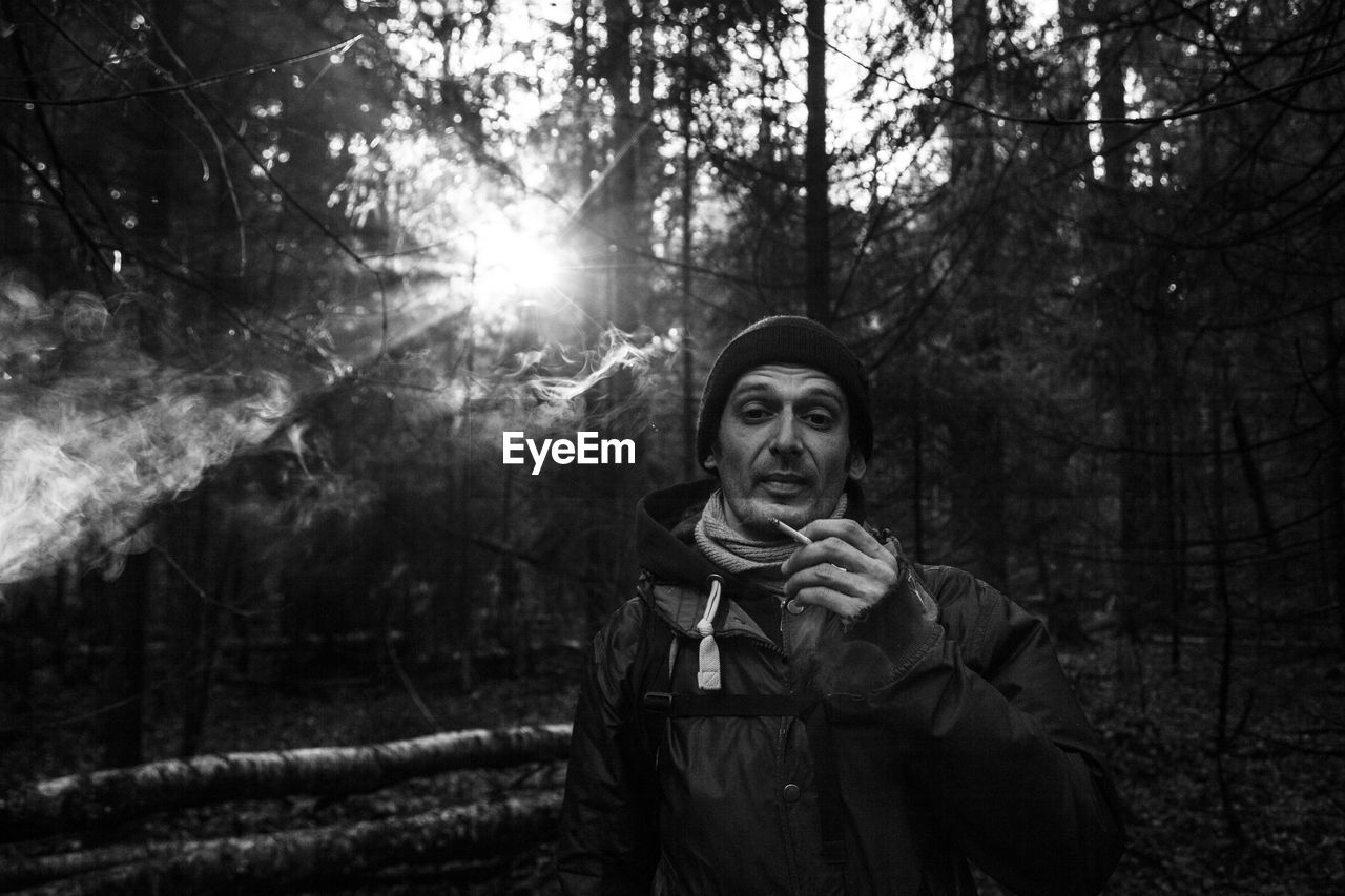 Portrait of man smoking in forest