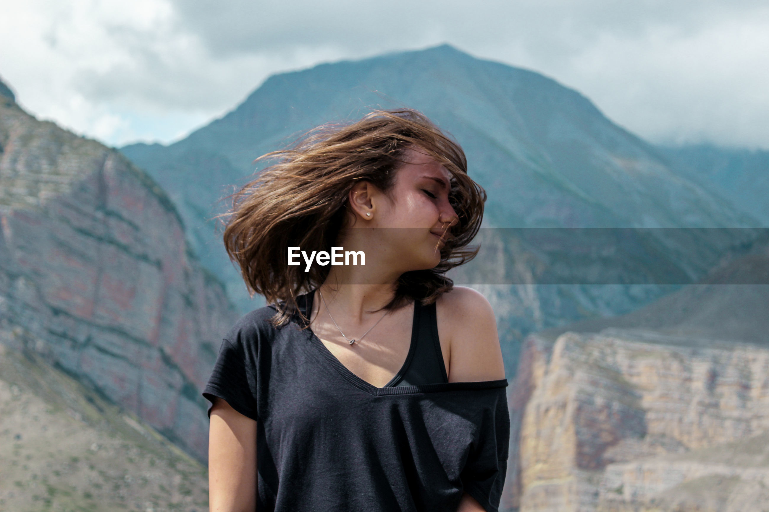 Young woman tossing her hair standing against mountain range
