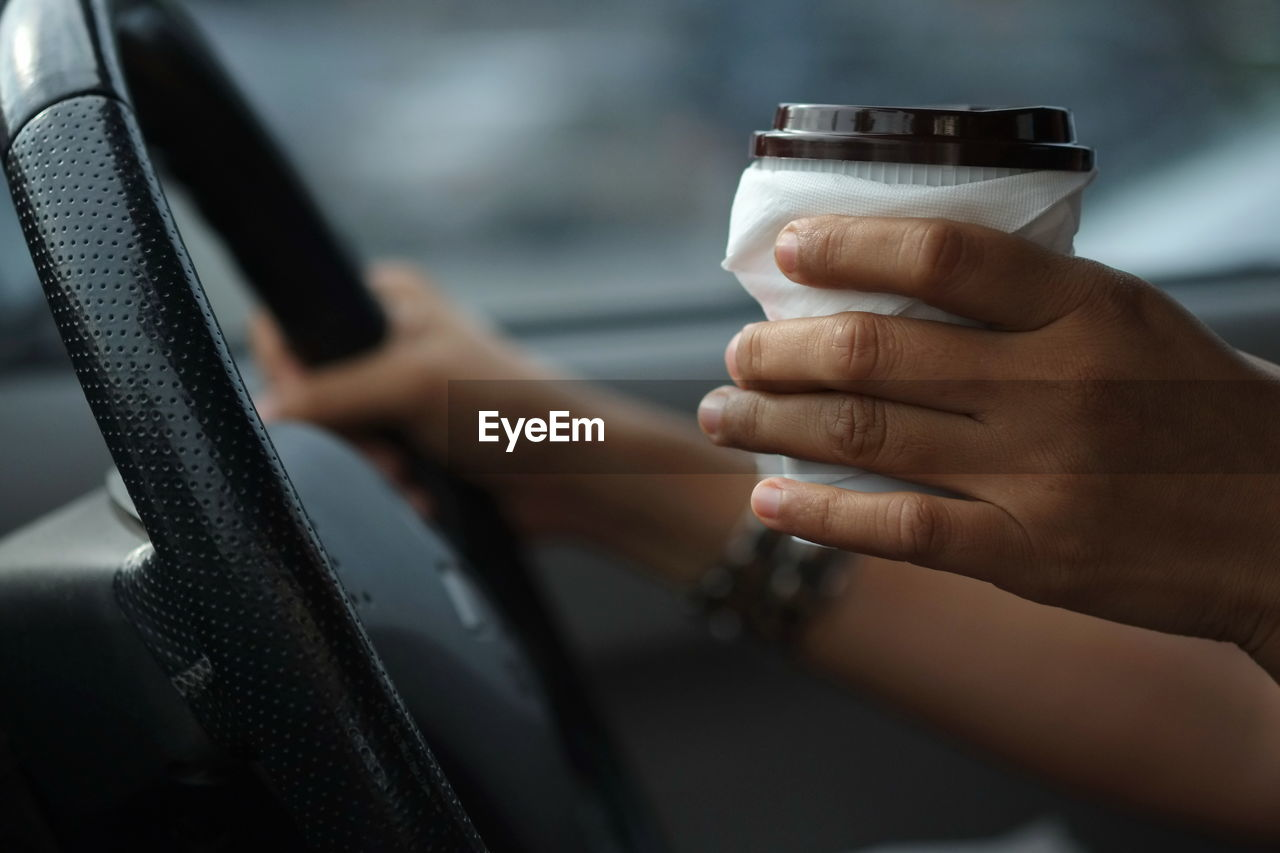 Close-Up Of Hand Holding Disposable Cup While Driving Car