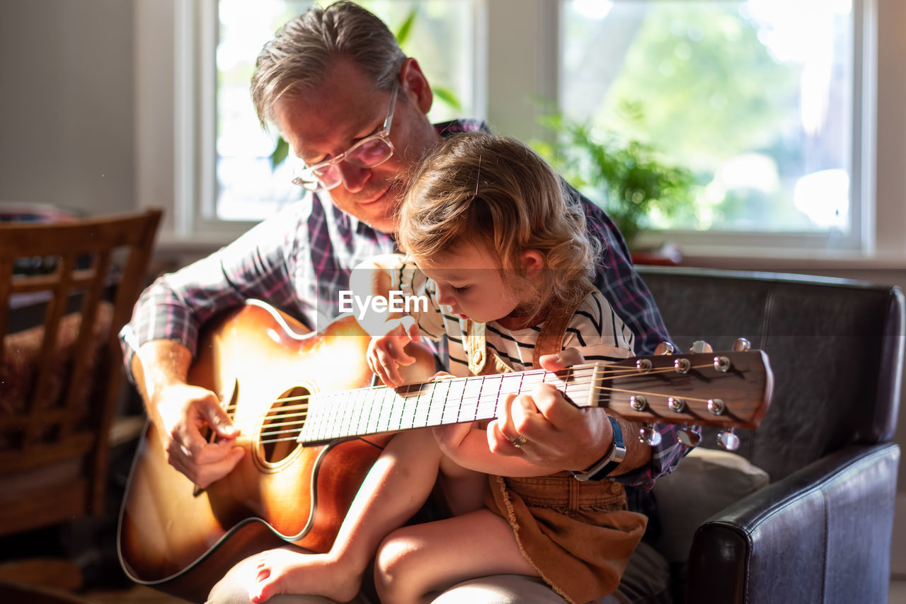 Grandfather teaching guitar to granddaughter at home