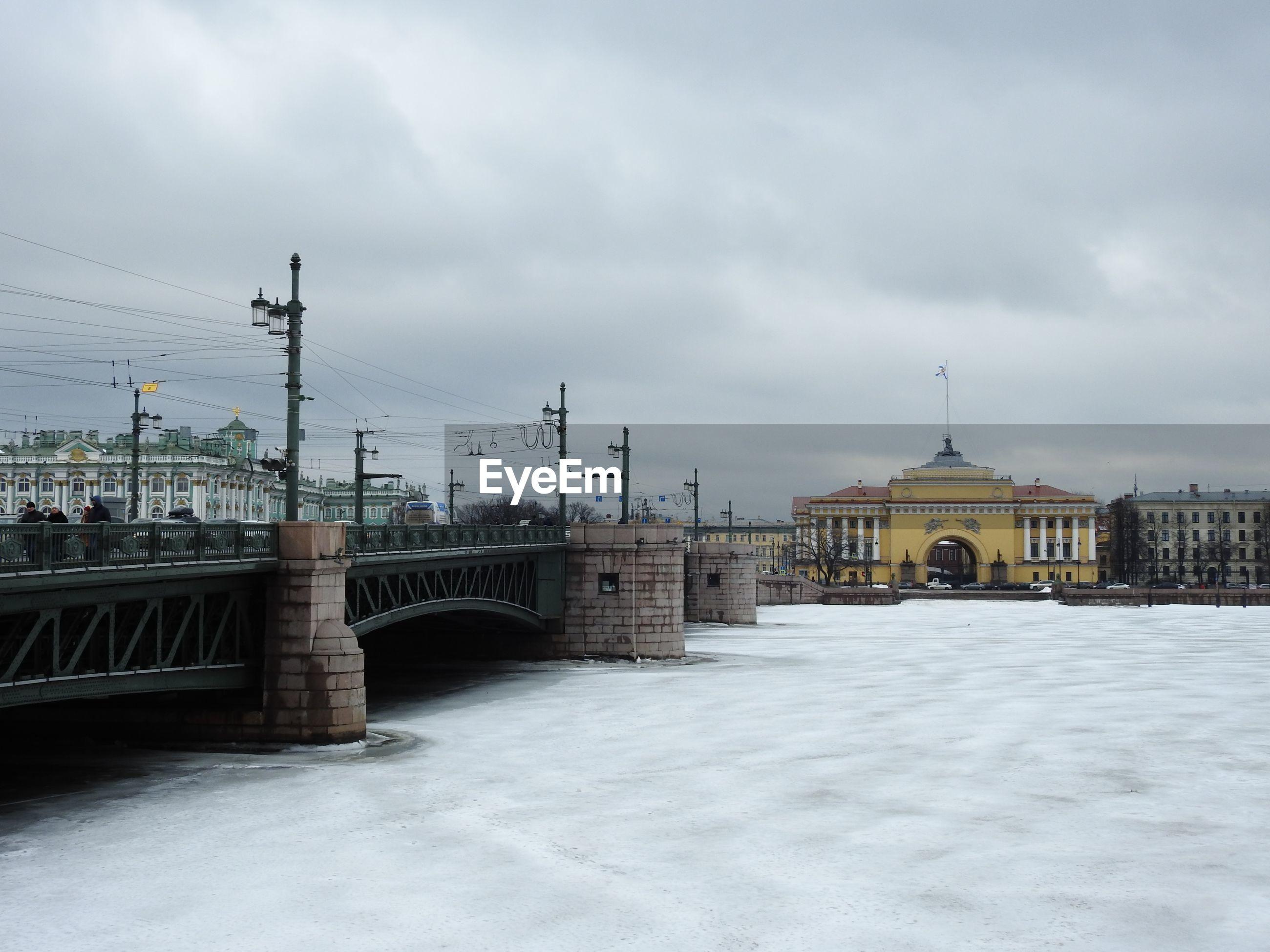 Bridge over buildings in city against sky