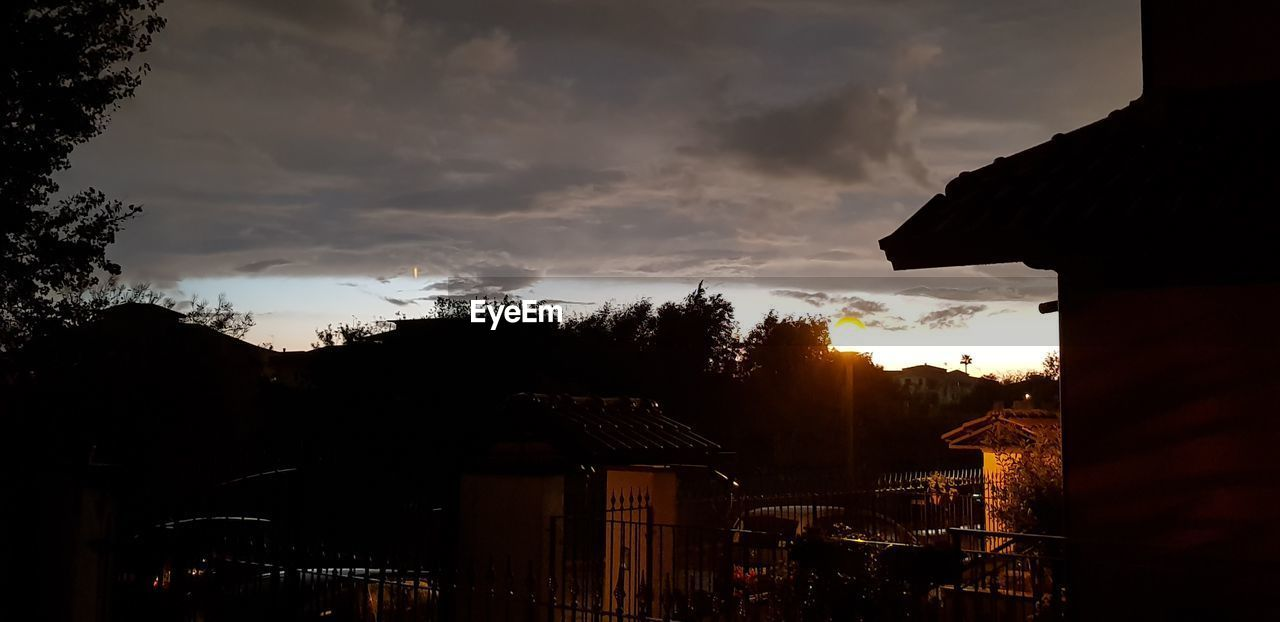sky, cloud - sky, architecture, building exterior, built structure, silhouette, sunset, building, nature, tree, no people, dusk, outdoors, city, residential district, beauty in nature, plant, dramatic sky, house, ominous