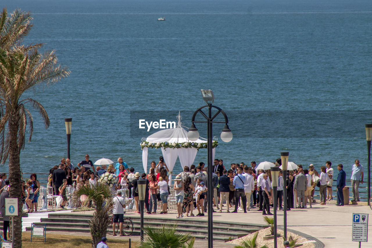 Group of people standing on promenade by sea in city