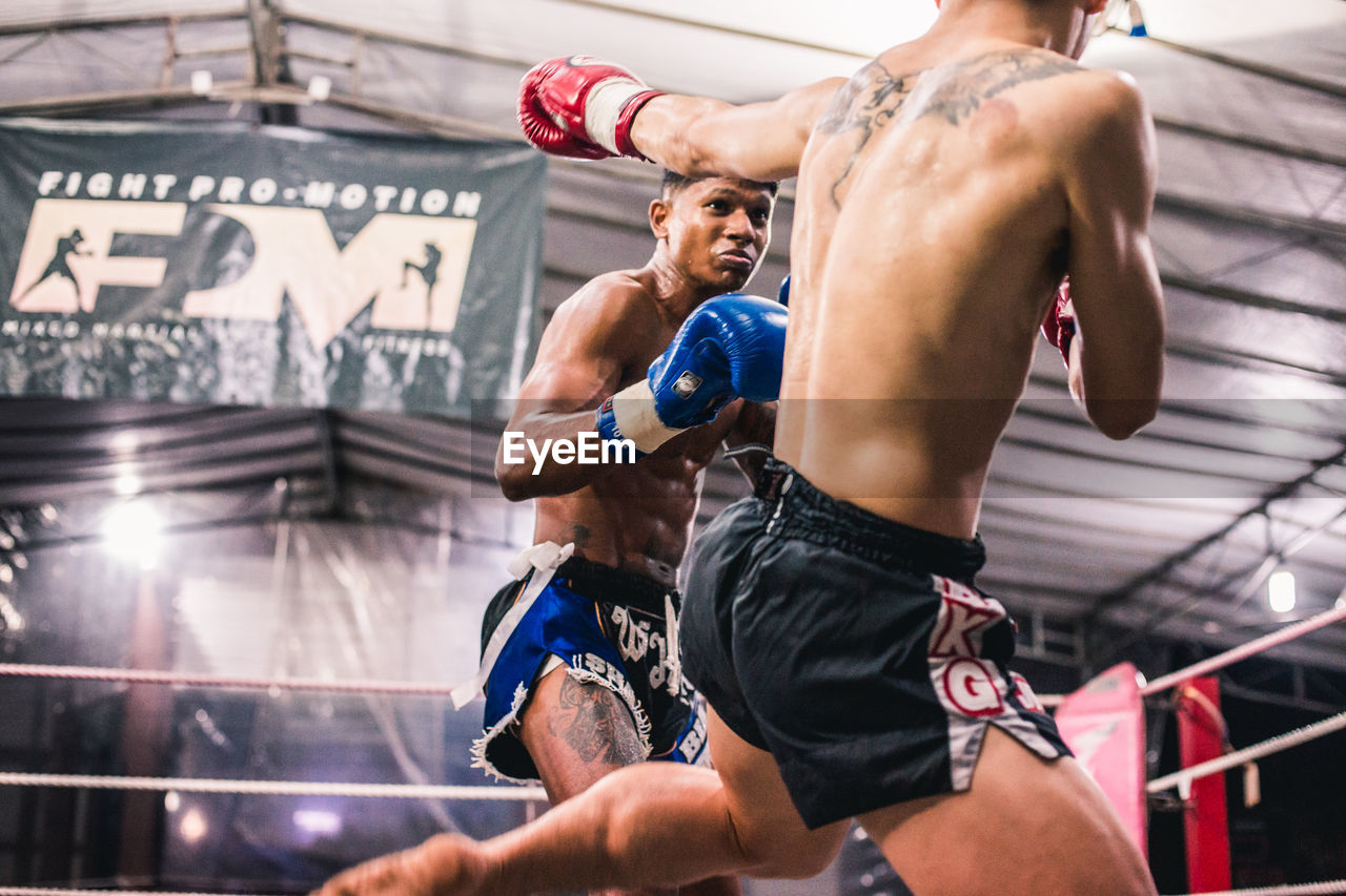 sport, strength, muscular build, healthy lifestyle, lifestyles, men, real people, vitality, shirtless, athlete, exercising, adult, two people, determination, clothing, males, people, sports training, focus on foreground, effort, shorts