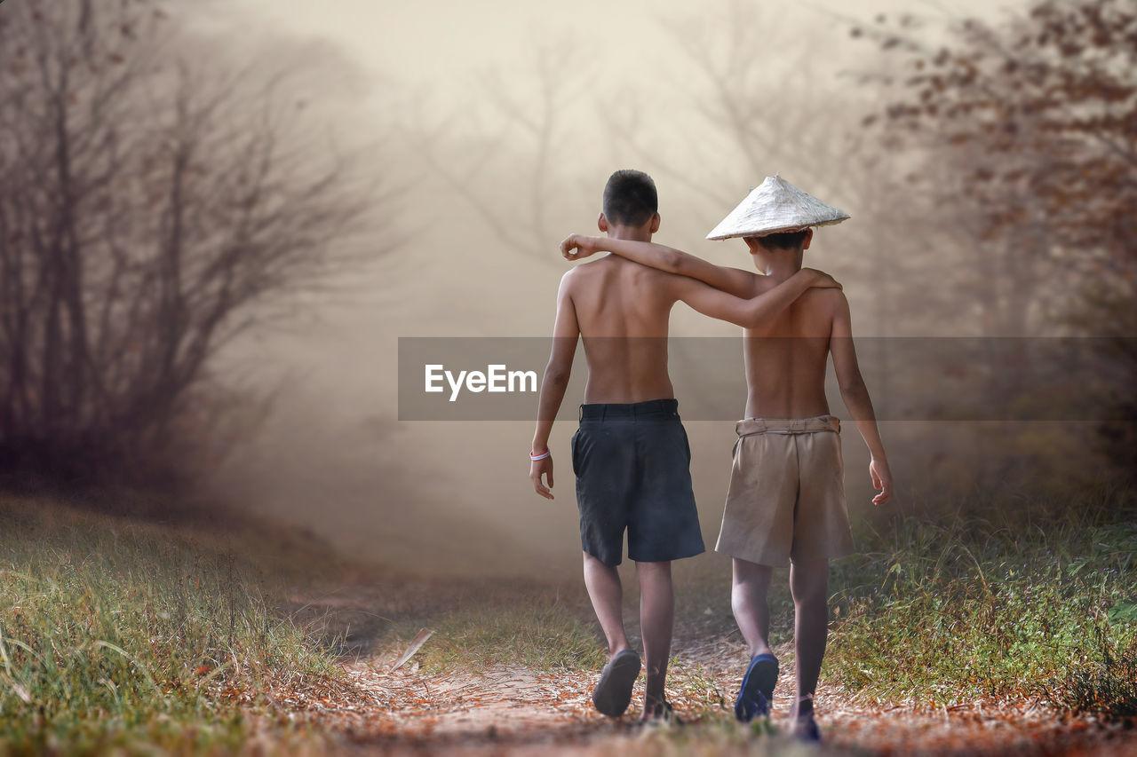 Rear View Of Friends Walking On Field