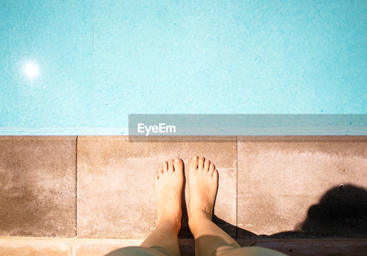 LOW SECTION OF WOMAN RELAXING IN SWIMMING POOL AGAINST WALL