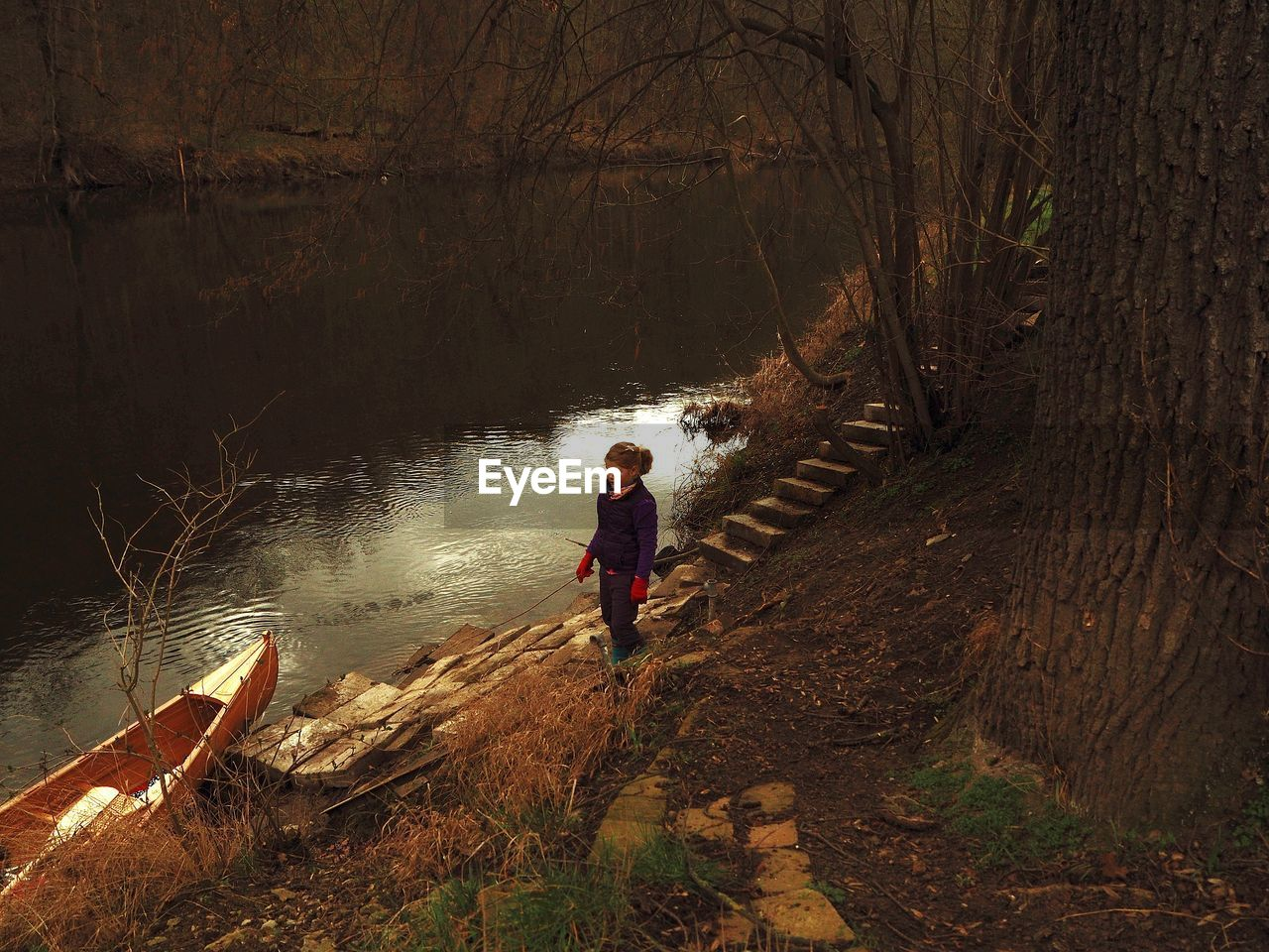 High angle view of girl standing by lake in forest